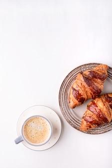 Croissants y una taza de café en una mesa de madera blanca