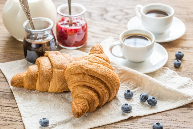 Croissants con tazas de café y leche.