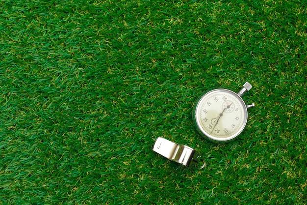 Cronómetro plateado sobre hierba verde