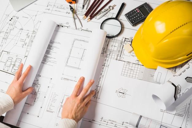 Crop architect opening blueprint Foto gratis