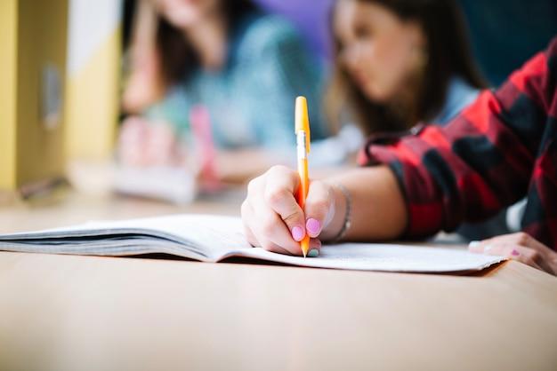 Crop estudiante de escribir en el bloc de notas