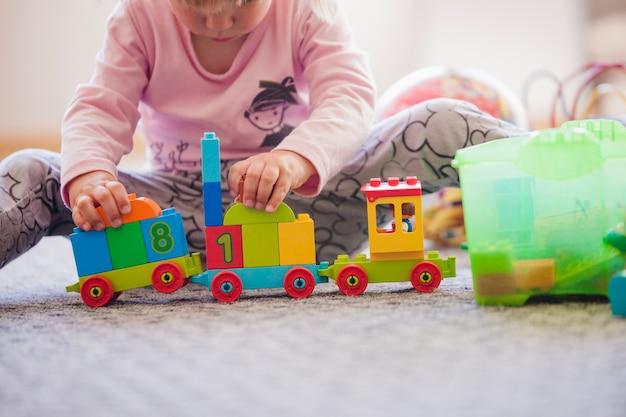 Crop niño con juguetes en el piso