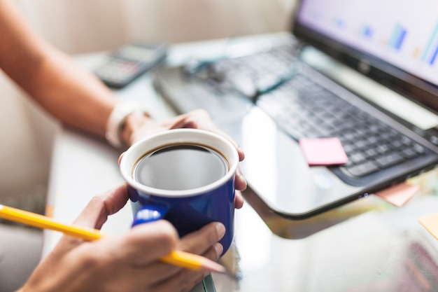 Crop persona tomando café en la oficina