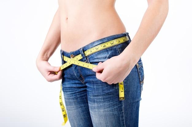 Cropped imagen de mujer medir su cintura