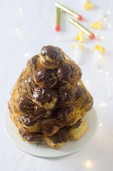 Croquembush hecho de profiteroles con crema pastelera y chocolate, decorado con hilos de caramelo.