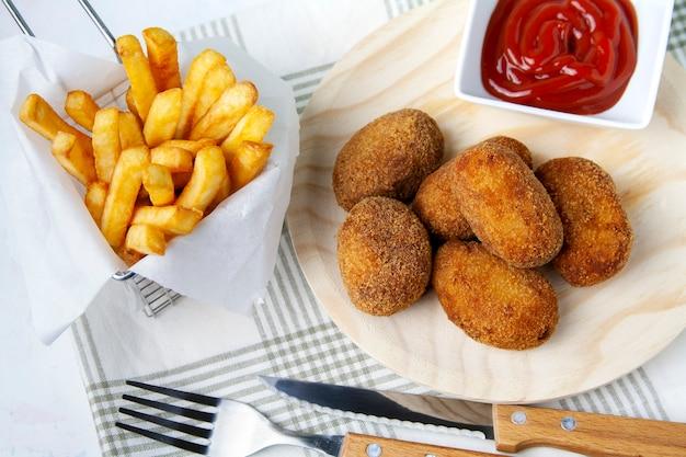 Croquetas con patatas fritas y tomate frito.