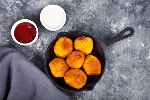 Croquetas de patatas en la sartén de hierro y salsas.