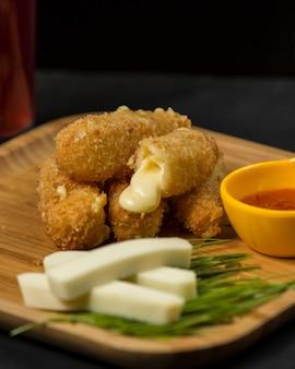 Croquetas de queso sobre tabla de madera