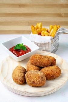 Croquetas sobre un plato de madera con tomate y patatas fritas.