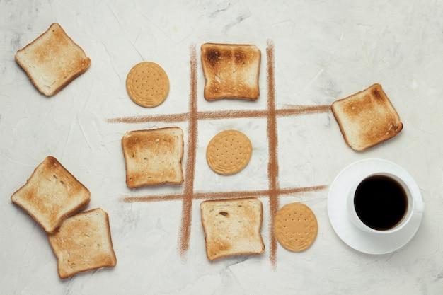 Crosses choice game competition cookie y tostadas tostadas cuadradas, taza con café negro, piedra blanca