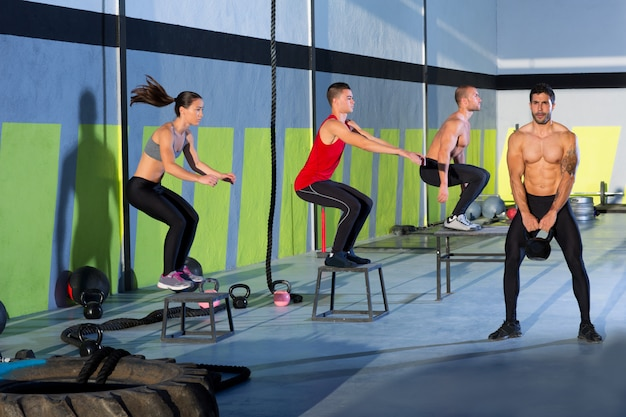 Crossfit box jump people group y kettlebell man.