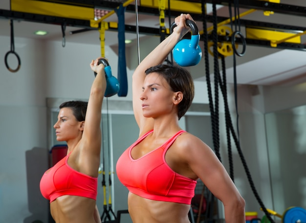 Crossfit fitness levantamiento de pesas kettlebell mujer en el espejo
