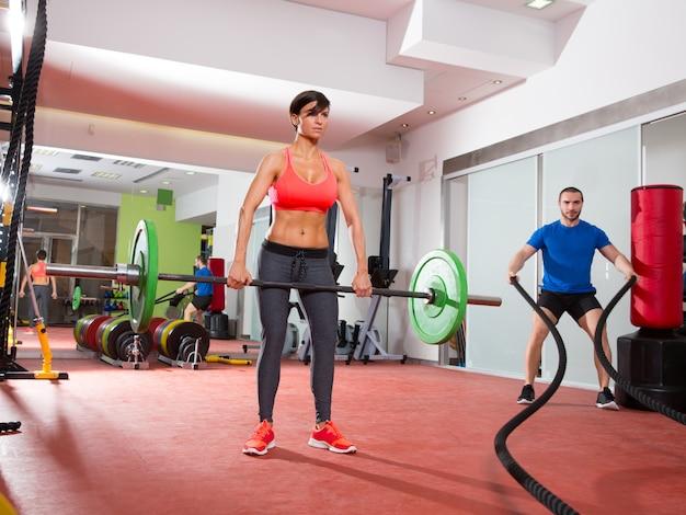 Crossfit gimnasio levantamiento de pesas bar mujer hombre luchando cuerdas