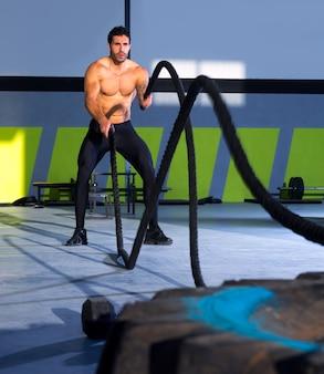 Crossfit luchando cuerdas en el ejercicio de entrenamiento de gimnasio