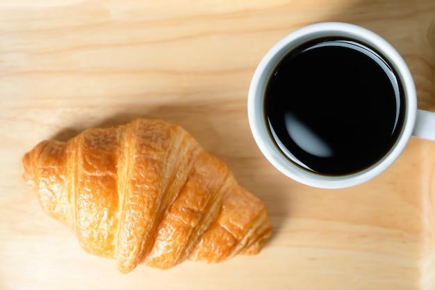 Cruasanes y café en fondo de madera.