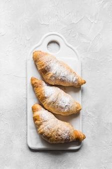 Cruasanes hechos en casa frescos en la bandeja de la hornada con el papel de la hornada. concepto de panadería francesa.