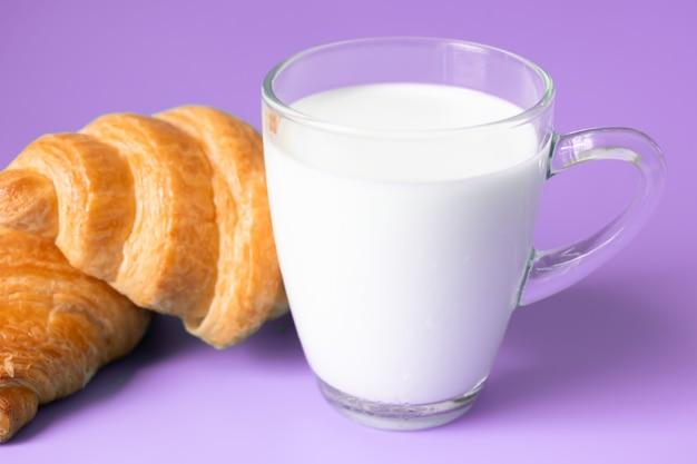 Cruasanes y leche en fondo del color.