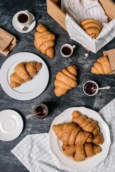Cruasanes, olla con mermelada y taza de café a un lado en la mesa gris