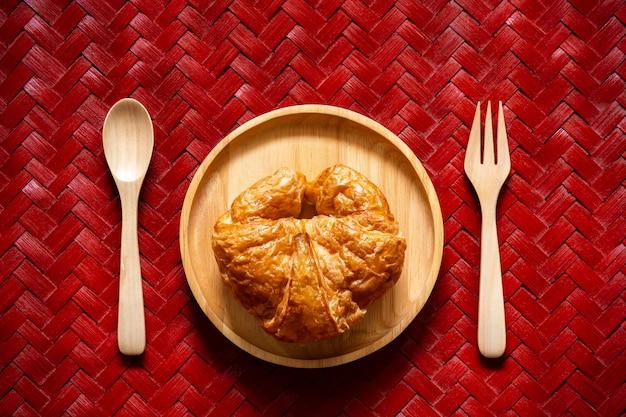 Cruasanes en plato de madera con la cuchara y la bifurcación.