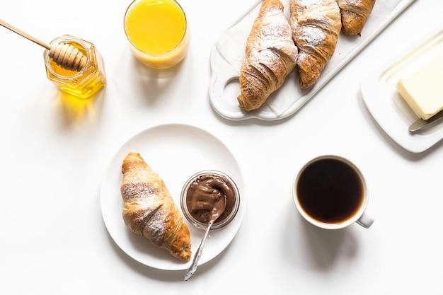Cruasanes y taza de café recientemente cocidos en blanco. desayuno francés.