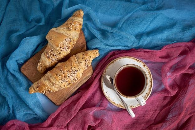 Cruasanes y taza frescos de té negro en fondo colorido.