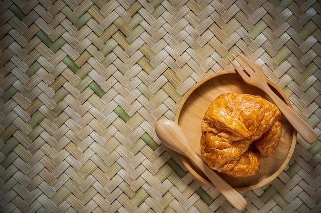 Cruasanes de la visión superior en plato de madera con la cuchara y bifurcación en textura del bambú tejido.