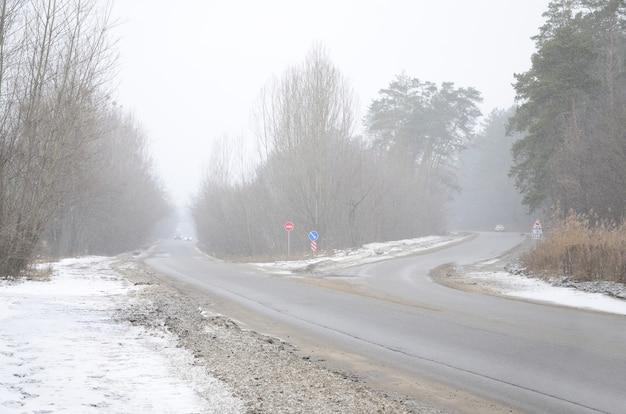 Cruce de caminos en una carretera asfaltada suburbana en invierno durante una tormenta de nieve