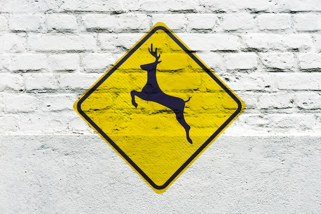 Cruce de ciervos: señal de tráfico estampada en la pared blanca, como graffiti
