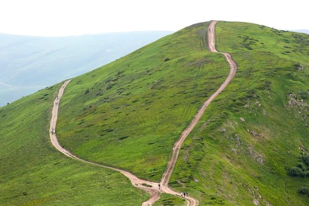 Cruce de dos caminos caminos de ripio con excursionistas turistas que viajan en las montañas de los cárpatos, ucrania.