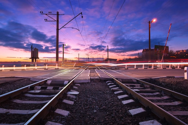 Cruce de ferrocarril con las luces del automóvil en movimiento por la noche