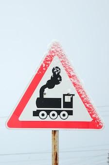 Cruce ferroviario sin barrera. una señal de tráfico que representa una vieja locomotora negra.
