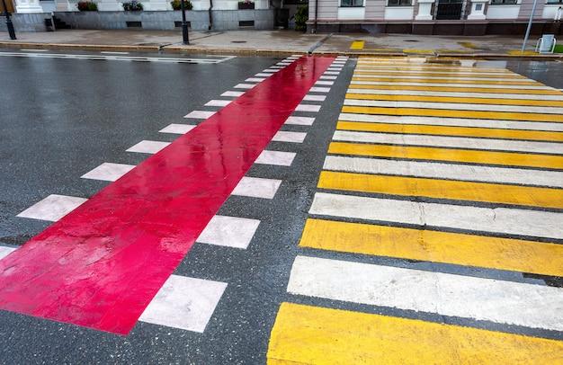 Cruce peatonal con líneas blancas, amarillas y rojas.