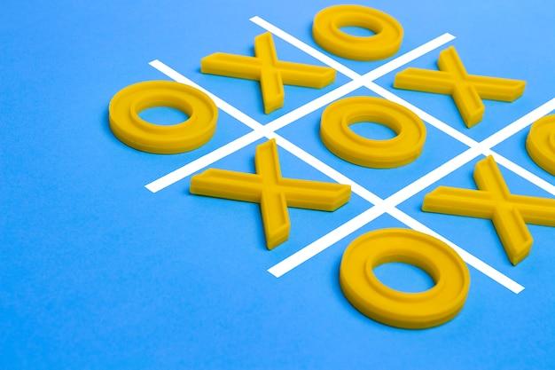Cruces de plástico amarillas y un dedo del pie y un campo reglado para jugar tres en raya sobre una superficie azul. concepto xo win challenge. juego educativo para niños