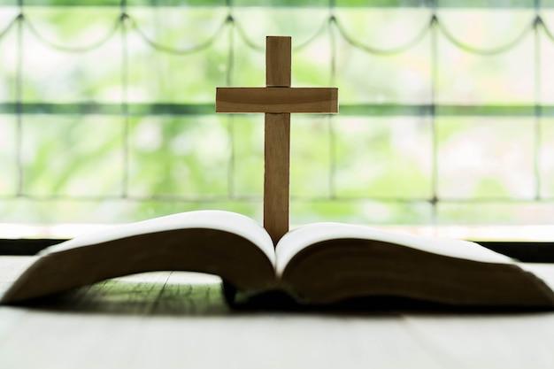 Cruces que se abren sobre la biblia en una mesa de madera.
