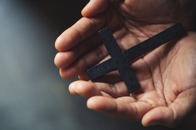 Crucifijo cruz en la mano de fondo.