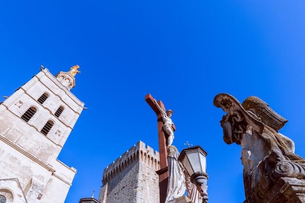 Crucifixión de jesús en la plaza frente a la catedral de nuestra señora de las doms palacio de los papas en la ciudad de aviñón