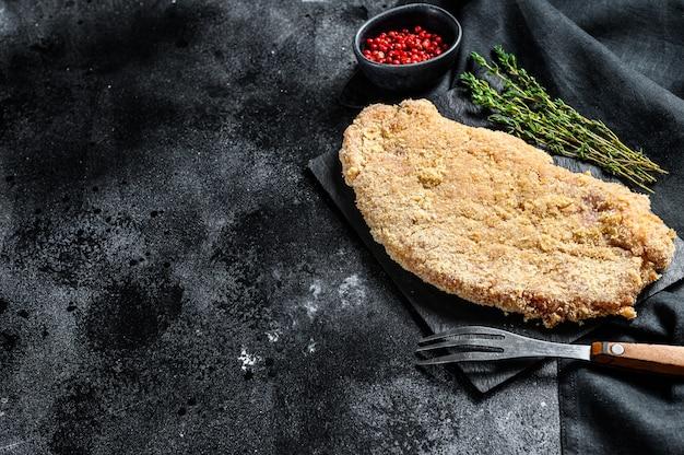 Crudo wiener schnitzel, filete empanado listo para cocinar. fondo negro. vista superior. copia espacio