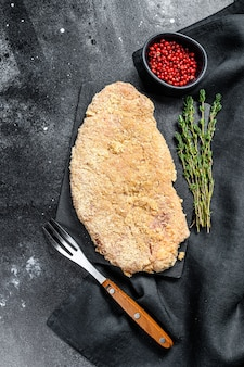 Crudo wiener schnitzel, filete empanado listo para cocinar. fondo negro. vista superior