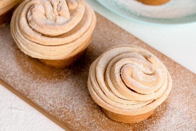 Cruffins pasteles de primavera de pascua, muffin y croissant roll sobre un fondo claro, primer plano para el lugar del texto. kulich festivo casero fresco.