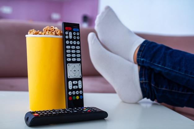 Crujiente caja de palomitas de caramelo dulce para merienda mientras mira televisión en casa