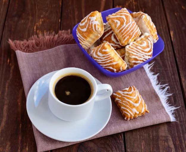 Crujiente galleta de hojaldre con chocolate blanco y taza de café negro sobre una mesa de madera