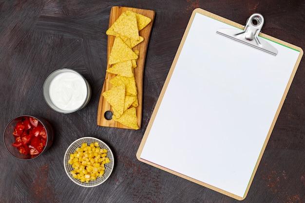 Crujiente portapapeles de verduras nachos y salsas blancas