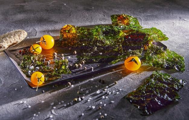 Crujientes algas nori con tomates cherry y especias oscuras sobre hormigón gris. comida japonesa nori. hojas secas de algas. copia espacio