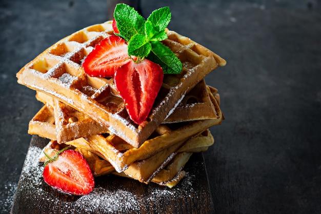 Crujientes gofres belgas con fresas maduras, menta y miel para el desayuno sobre un fondo claro.