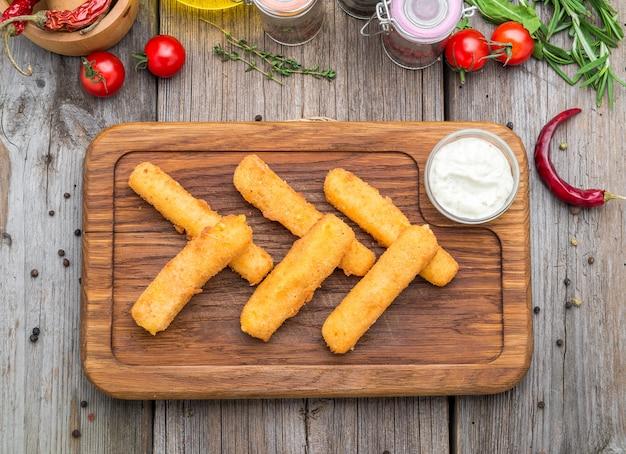 Crujientes palitos de queso mozzarella empanizados con salsa de mostaza. hermoso menú elegante.