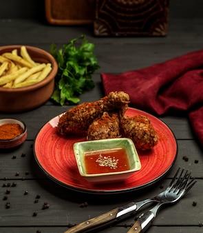Crujientes patas de pollo frito servidas con salsa de chile dulce y papas fritas