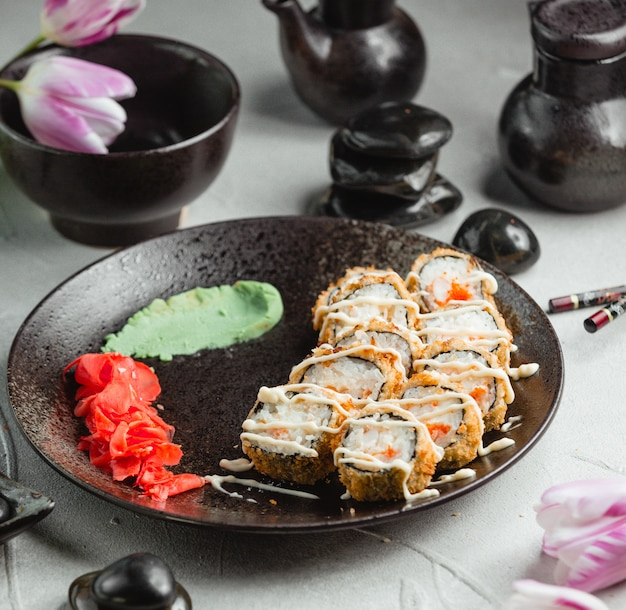 Crujientes rollos de sushi dentro de un plato negro.