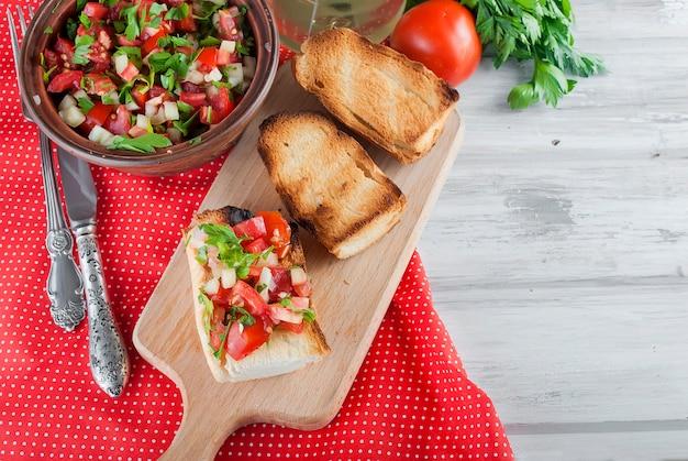 Crutones con ensalada de tomate y queso con hojas verdes.
