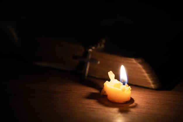 Cruz con biblia y vela sobre una vieja mesa de madera de roble.