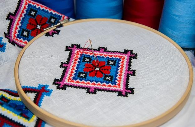 Cruz bordada con un patrón geométrico tradicional sobre un paño blanco